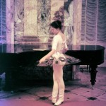 Ballerina sampling Lenin's piano. Marble Palace, St. Peterburg.1991.